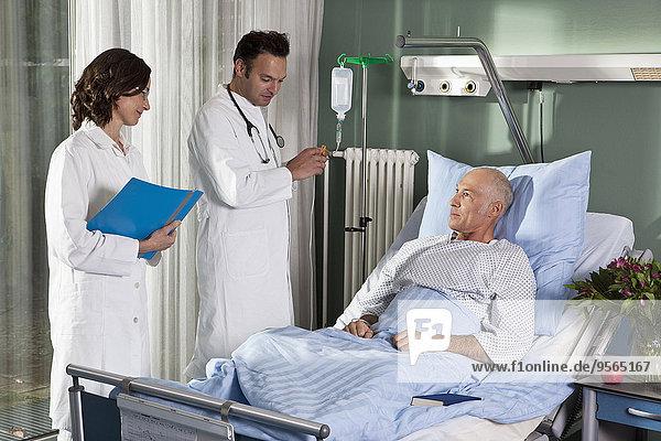 Zwei Ärzte mit einem männlichen Patienten auf einer Krankenstation