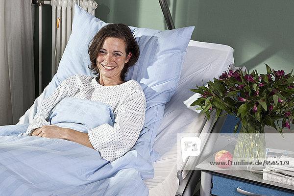 Porträt einer Frau im Krankenhausbett liegend