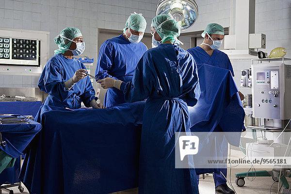 Ein OP-Team  das einen Patienten in einem Operationssaal operiert.