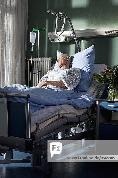Ein Mann  der in einem Krankenhausbett schläft.