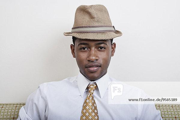 Ein junger schwarzer Mann mit Hut und Krawatte.