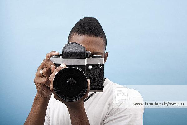 Ein junger schwarzer Mann mit einer altmodischen Kamera.