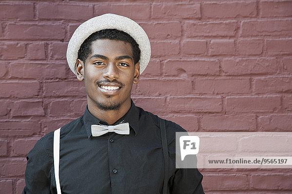 Ein fröhlicher junger schwarzer Mann mit Fliege  Hosenträgern und Hut.