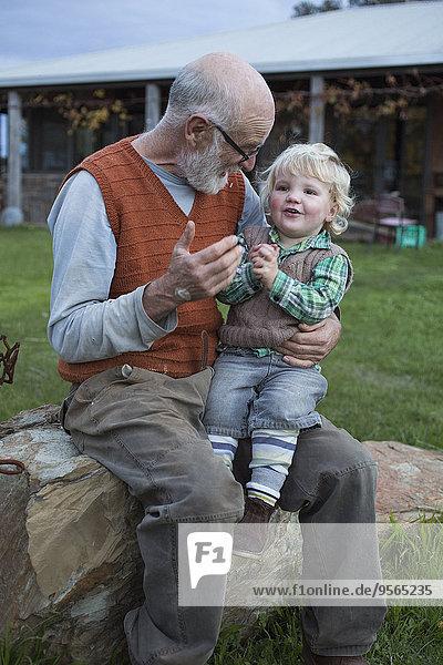 Süßer Junge auf Großvaters Schoß im Park sitzend
