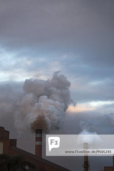 Rauch aus Schornsteinen gegen bewölkten Himmel