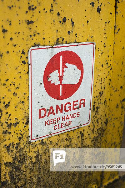 Warnschild an gelber Wand im Freien