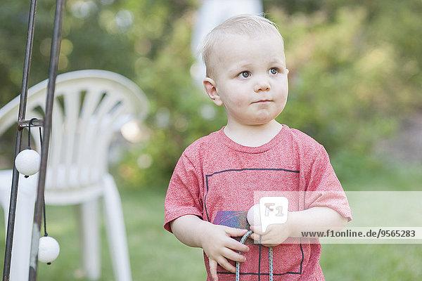 Süßer kleiner Junge  der wegguckt  während er Spielzeug im Park hält.