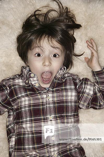 Porträt eines geschockten Jungen mit offenem Mund auf einem Teppich liegend