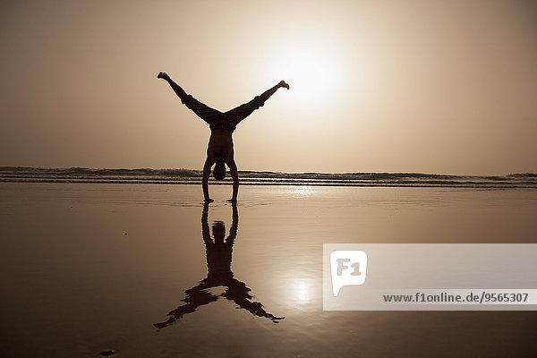 Volle Länge des Silhouetten-Mannes mit Handstand am Strand