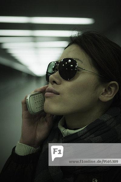 Nahaufnahme einer erwachsenen Frau mit Handy im Tunnel