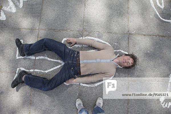 Hochwinkelansicht der Kreidekontur um den auf der Straße liegenden Mann