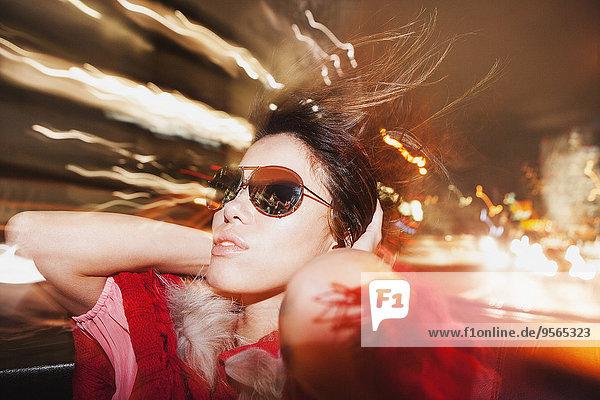 Glamouröse Frau mit Sonnenbrille genießt Autofahrt