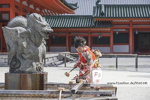 Mittlere erwachsene Frau beim Händewaschen gegen den Tempel