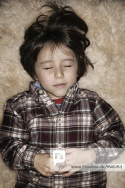 Süßer Junge schläft auf einem Teppich