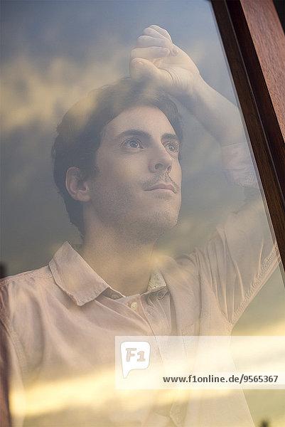 Mann schaut bei Sonnenuntergang aus dem Hotelfenster