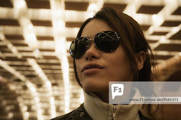 Nahaufnahme einer mittleren erwachsenen Frau mit Sonnenbrille im Tunnel