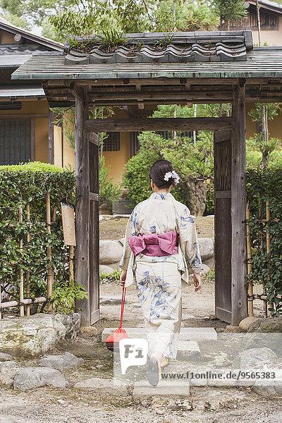 Durchgehende Rückansicht der Frau in traditioneller Kleidung am Eingangstor