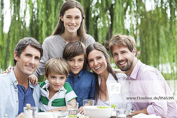 Familie posiert für Porträt bei einem Treffen im Freien