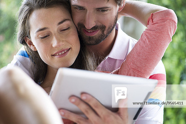 Young couple using digital tablet together outdoors