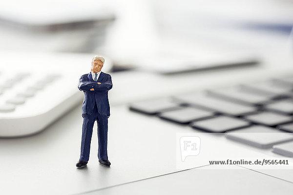 Geschäftsmann-Figur stehend auf Laptop-Tastatur