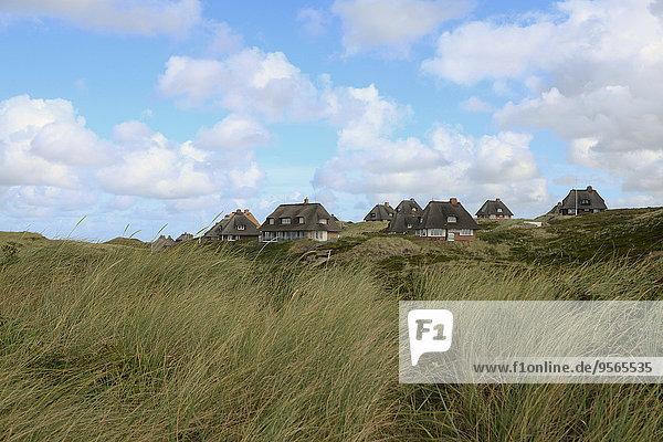 Häuser auf grasbewachsenem Feld gegen bewölkten Himmel