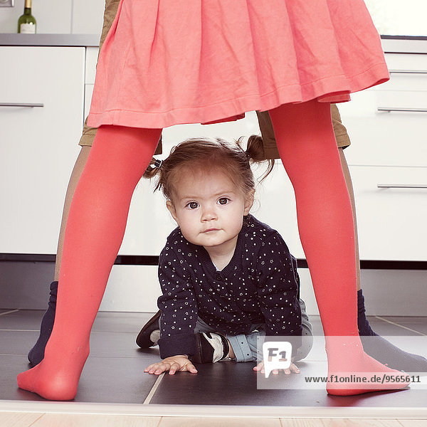 Kleines Mädchen krabbelt durch die Beine von Geschwistern Kleines Mädchen krabbelt durch die Beine von Geschwistern