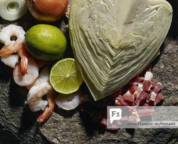 Nahaufnahme von Garnelen und geschnittenem Fleisch mit Gemüse auf Fels