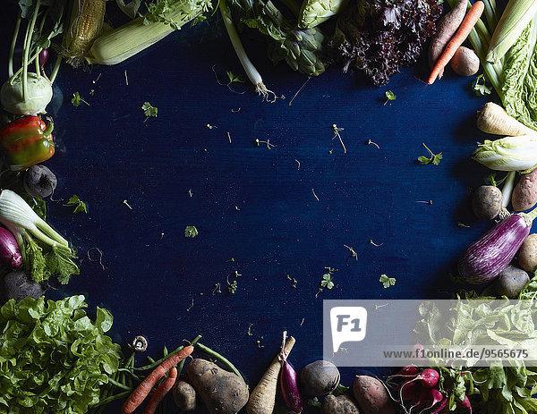 Direkt über dem Schuss frisches Gemüse und Früchte bilden einen Kreis auf blauem Tisch.