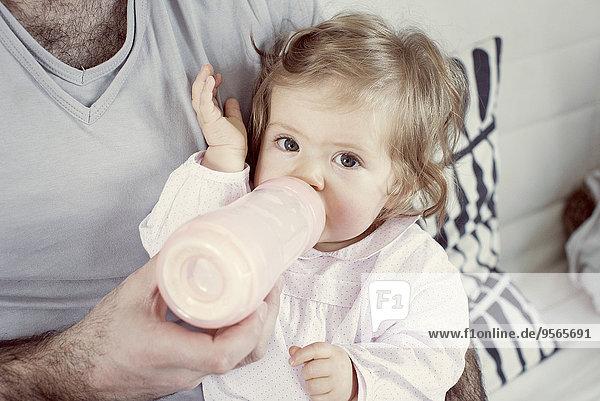 Kleines Mädchen auf Vaters Schoß sitzend  aus der Flasche trinkend  beschnitten Kleines Mädchen auf Vaters Schoß sitzend, aus der Flasche trinkend, beschnitten