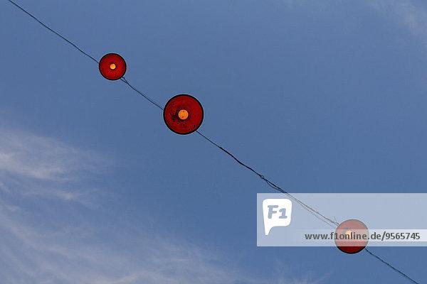 Niederwinkelansicht der am Kabel hängenden Lampen gegen den blauen Himmel