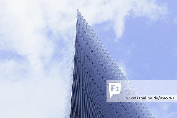 Flachwinkelansicht eines modernen Glasgebäudes gegen bewölkten Himmel