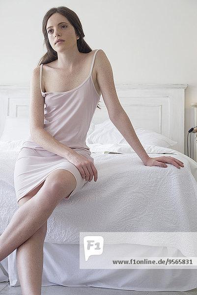 Frau auf Bettkante sitzend