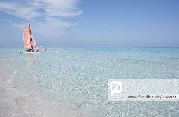 Mitteldistanz-Ansicht von Menschen  die mit einem Segelboot auf See gegen den blauen Himmel reisen.