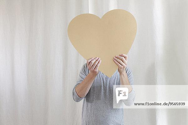Reifer Mann mit Herzform vor dem Gesicht zu Hause