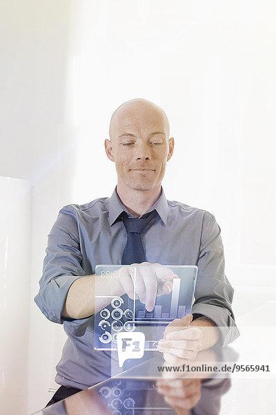 Geschäftsmann mit futuristischem Digital-Tablett am Schreibtisch im Büro