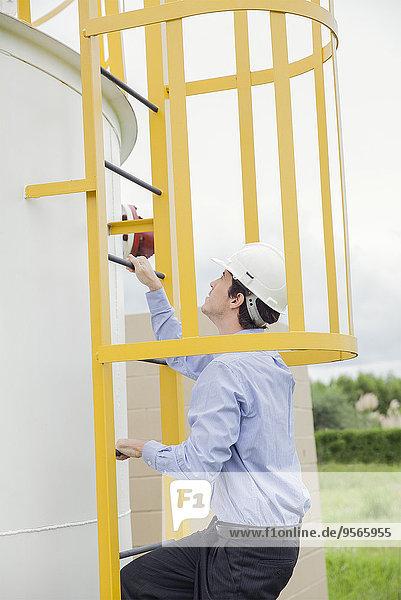 Ingenieur beim Aufstieg auf die Tankleiter im Industriegebiet
