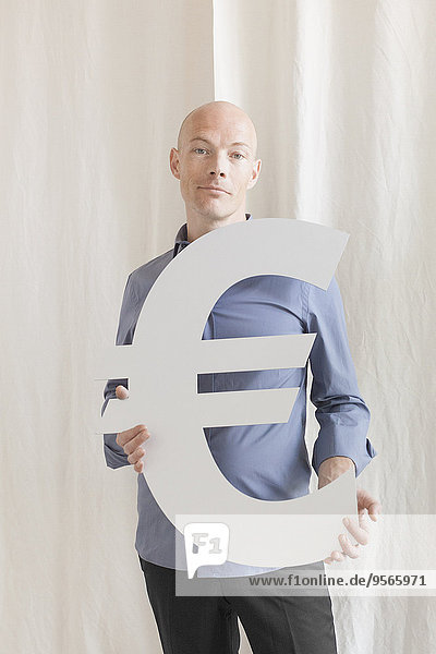 Porträt eines selbstbewussten Geschäftsmannes mit Euro-Symbol im Amt