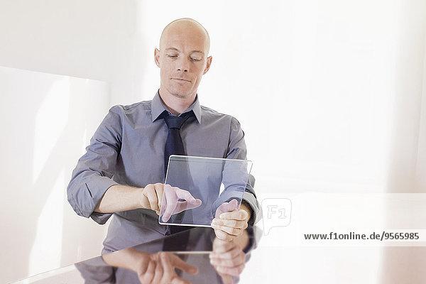 Geschäftsmann berührt futuristisches digitales Tablett am Schreibtisch im Büro