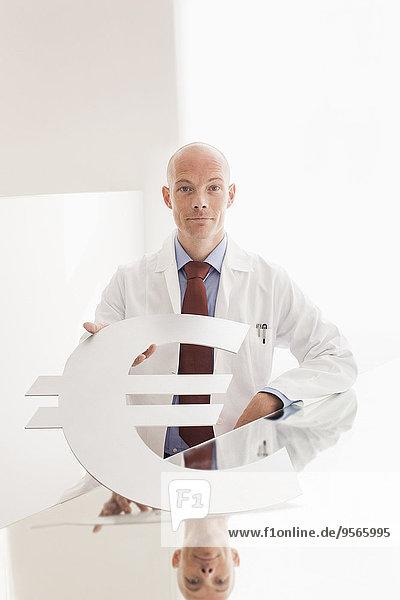 Porträt eines selbstbewussten Arztes mit Euro-Symbol am Schreibtisch in der Klinik