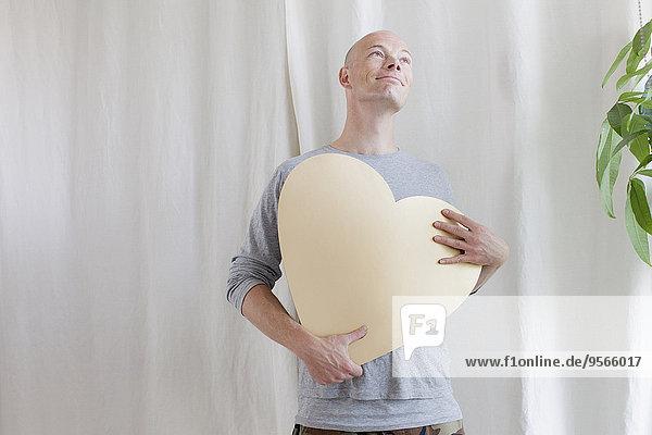 Reifer Mann mit Herzform zu Hause
