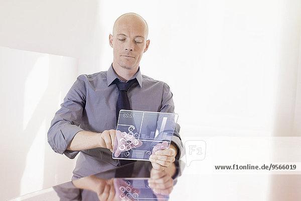 Geschäftsmann mit transparentem Digital-Tablett am Schreibtisch im Büro