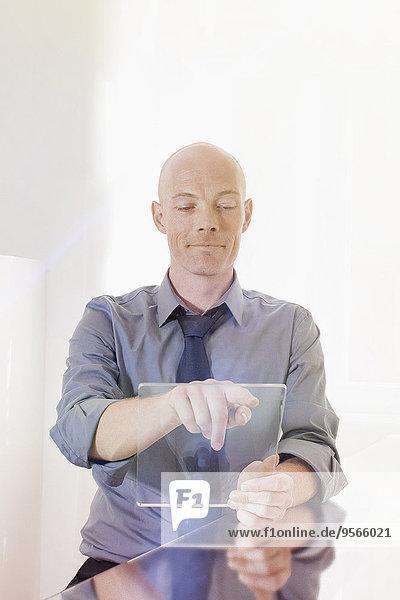 Geschäftsmann beim Berühren eines leeren futuristischen digitalen Tabletts am Schreibtisch im Büro