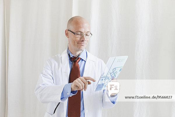 Lächelnder Arzt berührt futuristisches digitales Tablett in der Klinik