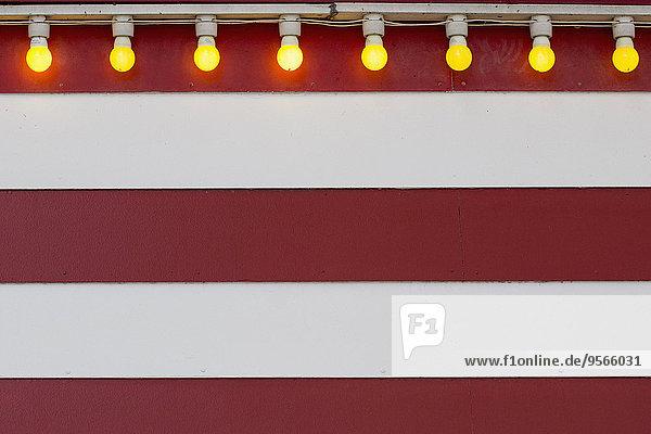 Beleuchtete Glühbirnen an gestreifter Wand