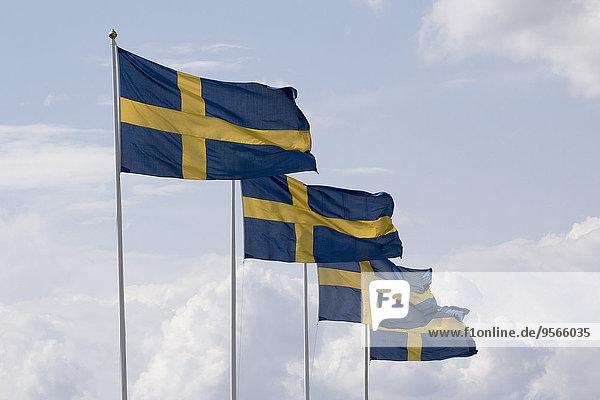 Reihe schwedischer Fahnenmasten gegen bewölkten Himmel