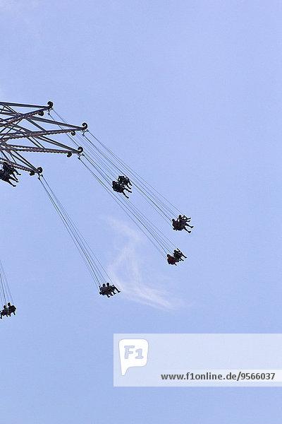 Tiefblick auf die Menschen  die auf einer Kettenschaukel gegen den blauen Himmel fahren.