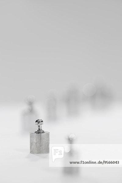 Selektiver Fokus auf kleines Metallgewicht vor grauem Hintergrund