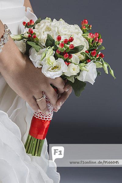 Mittelteil des Brautstraußes vor grauem Hintergrund