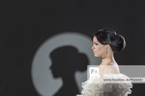 Spot beleuchtete schöne Braut schaut weg vor schwarzem Hintergrund