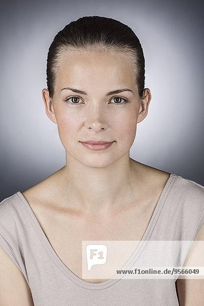 Nahaufnahme der schönen jungen Frau vor grauem Hintergrund